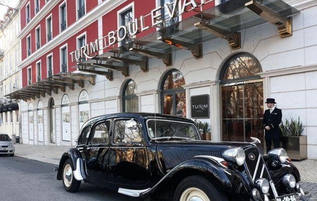 Fachada do Turim Boulevard hotel, com carro antigo e porteiro