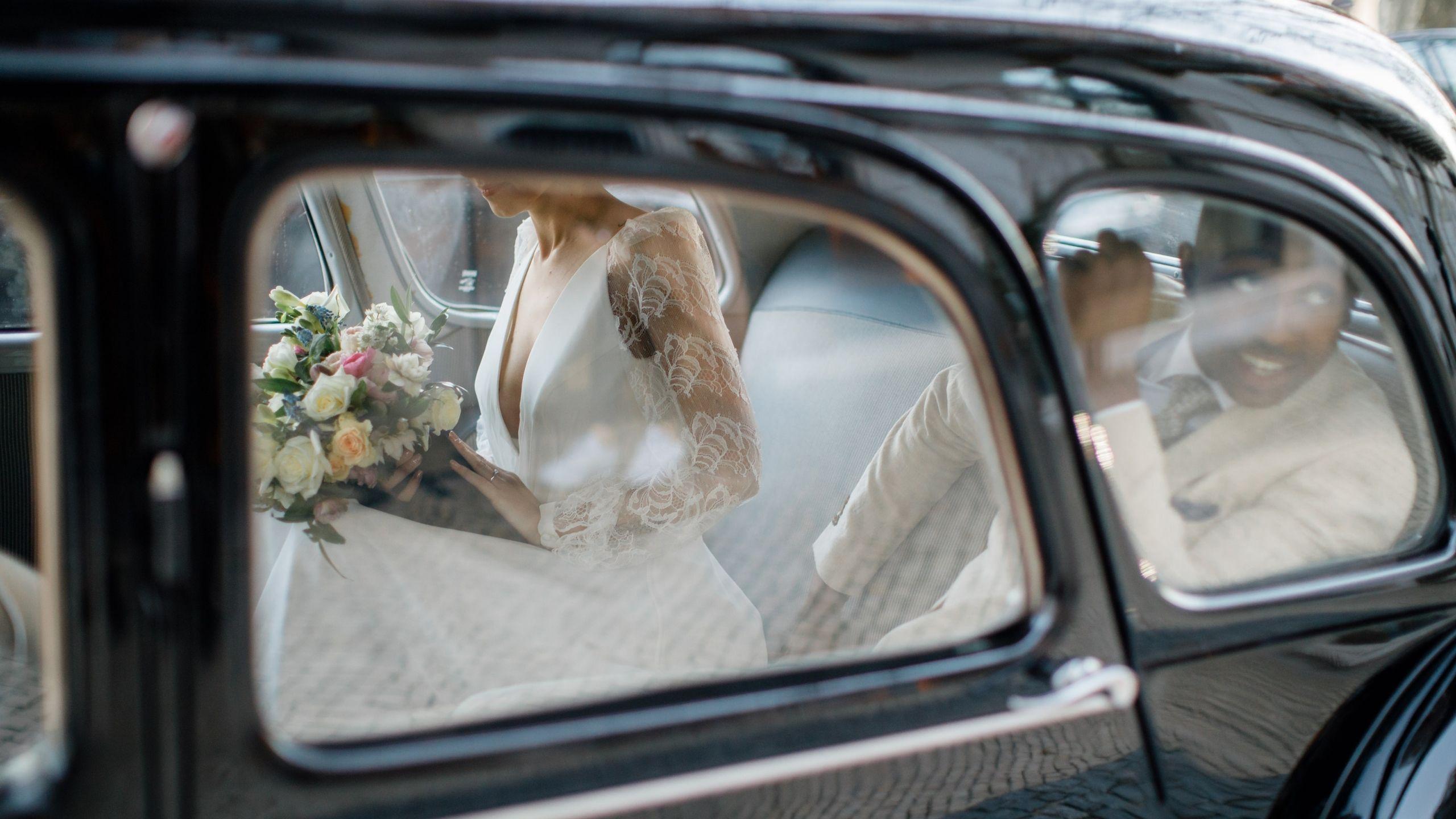 Noivos dentro de um carro antigo