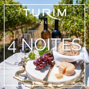 Vinha com copos de vinho, garrafas de vinho, cesto de pão, uvas e queijo